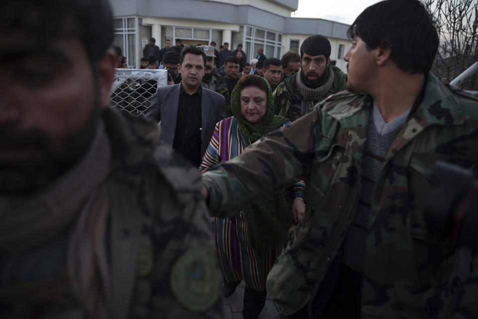 Hawa Alam Nuristani, chief of Election Commission of Afghanistan, center, leaves after a press conference at the commission's office in Kabul, Afghanistan, Tuesday, Feb. 18, 2020. Afghanistan's independent election commission says President Ashraf Ghani has won a second term as president in a vote that took place on Sept. 28 last year. (AP Photo/Rahmat Gul)