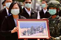 Taiwan President Tsai Ing-wen receives a framed photograph from a masked soldier during the COVID-19 coronavirus pandemic during a visit to a military base in Tainan on April 9, 2020