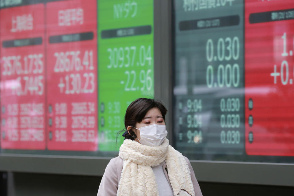 A woman walks by an electronic stock board of a securities firm in Tokyo, Wednesday, Jan. 27, 2021. Stocks were mixed in Asia on Wednesday after a lackluster session on Wall Street. (AP Photo/Koji Sasahara)