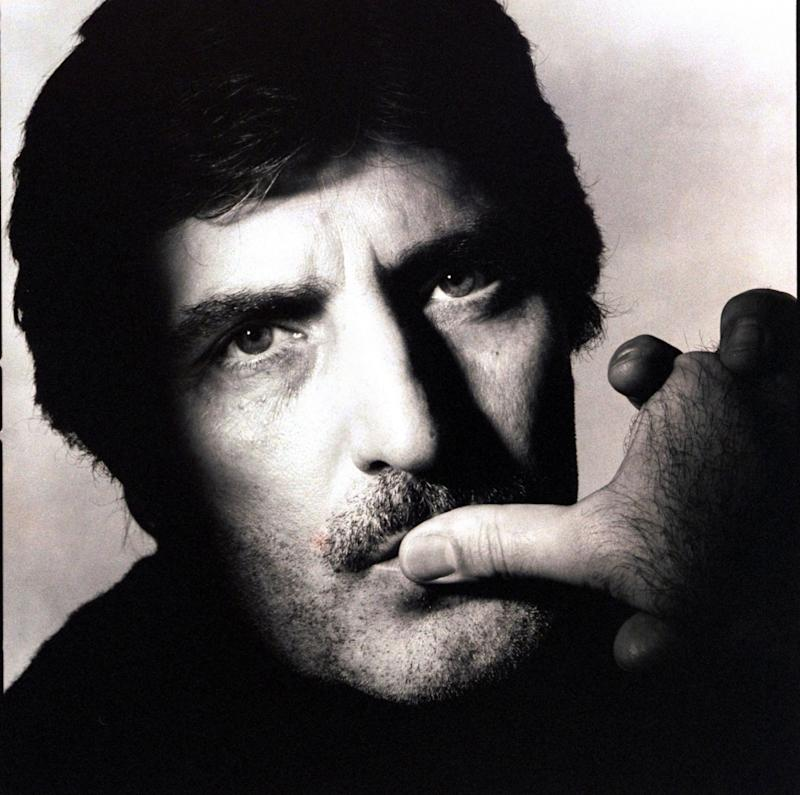 Headshot of fashion designer, Emanuel Ungaro, with moustache and a three-day beard, with his thumb on his lips, with a serious look