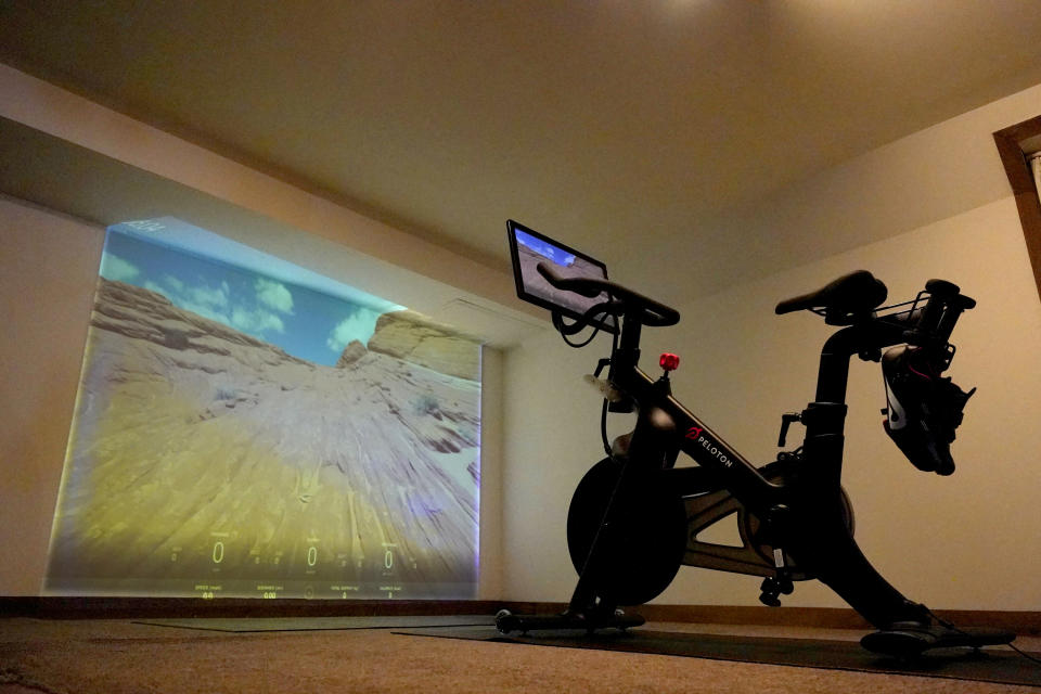 A projection of a desert scene is casted onto a wall near a Peloton fitness bike in a basement home gym, Tuesday, Sept. 15, 2020, in Lutherville-Timonium. Home gyms have picked up in 2020 with sales of exercise bikes going up during the COVID-19 pandemic. (AP Photo/Julio Cortez)