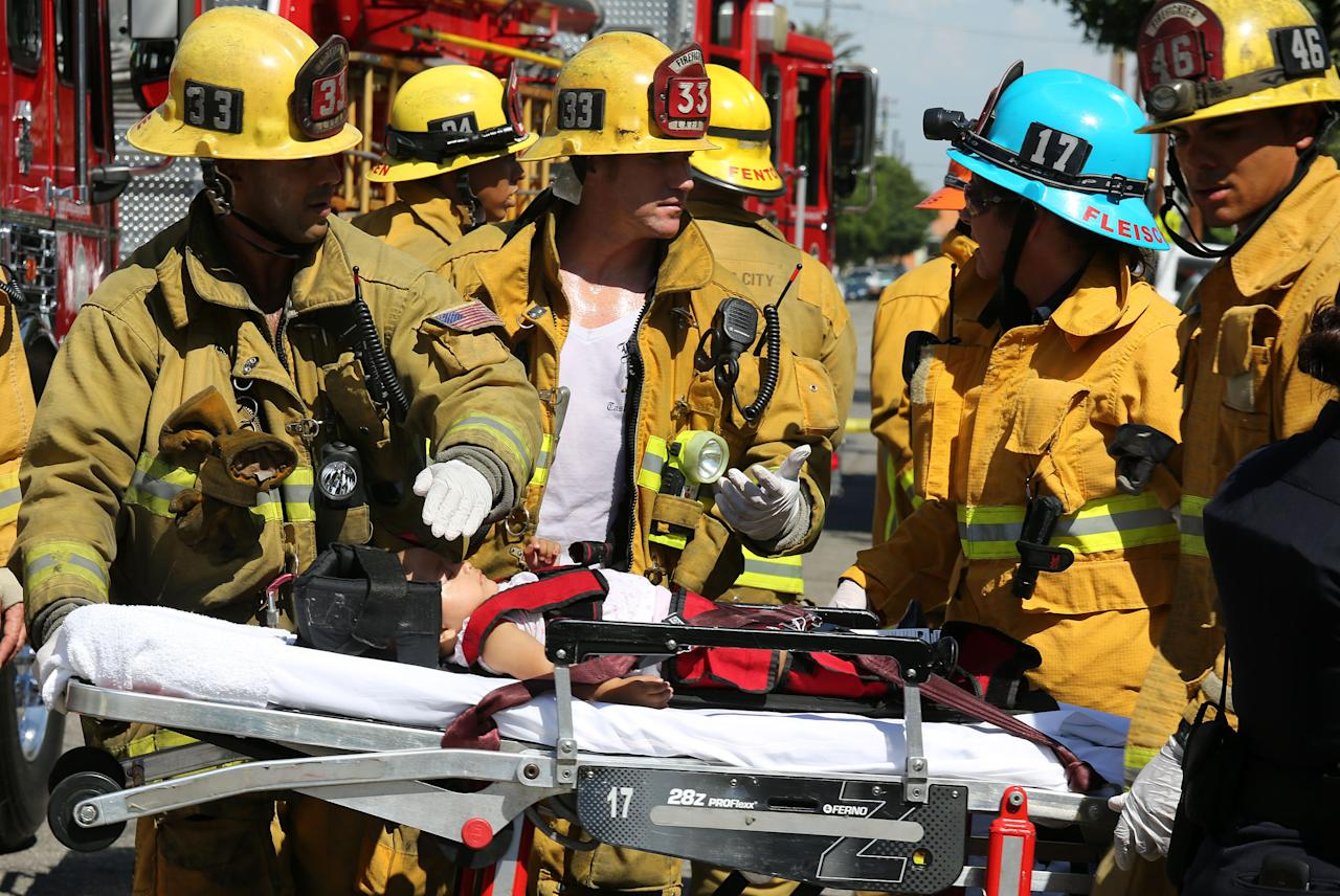 Los Angeles City Firefighter paramedics assist a child, one of eight people injured when a car sped onto a sidewalk and plowed into a group of parents and children outside Main Street Elementary school, Wednesday Aug. 29, 2012 in Los Angeles. The crash occurred at 2:50 p.m., shortly after school had let out for the day, according to a statement from the Los Angeles Unified School District. (AP Photo/La Opinion, J. Emilio Flores)