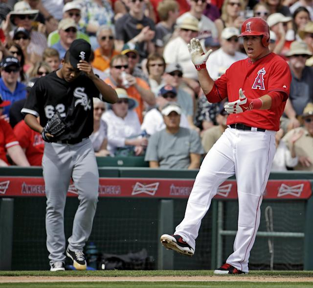 Los Angeles Angels' Mike Trout reacts from third in front of Chicago White Sox's Jose Quintana (62) after Trout hit a triple during the first inning of an exhibition spring training baseball game Thursday, March 13, 2014, in Tempe, Ariz. (AP Photo/Morry Gash)