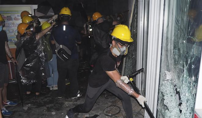 Protesters smashing windows during the storming of the Legislative Council building on July 1. Photo: Antony Dickson