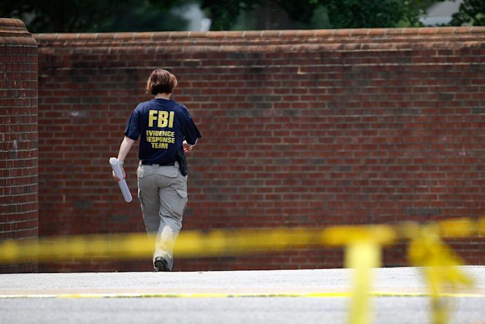 A member of the FBI walks down a ramp to enter a municipal building that was the scene of a shooting, Sunday, June 2, 2019, in Virginia Beach, Va. (Photo: Patrick Semansky/AP)
