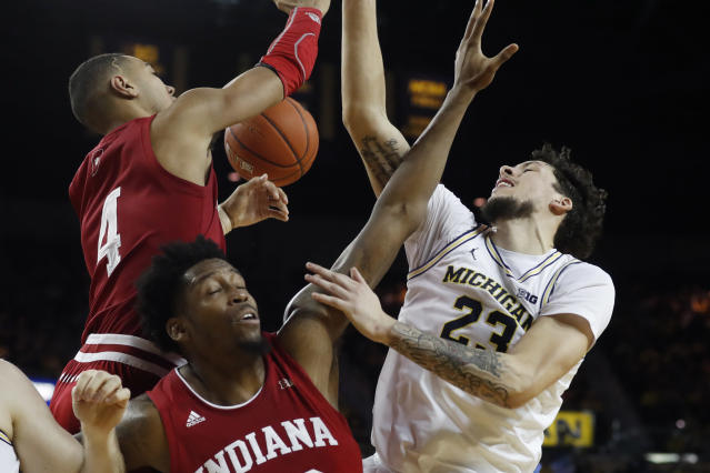 Indiana forwards Trayce Jackson-Davis (4) and De'Ron Davis and Michigan forward Brandon Johns Jr. (23) loose control of a rebound during the second half of an NCAA college basketball game Sunday, Feb. 16, 2020, in Ann Arbor, Mich. (AP Photo/Carlos Osorio)