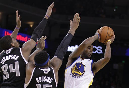 Golden State Warriors' Dorell Wright (1) looks to pass away from Sacramento Kings' JasonThompson (34) and DeMarcus Cousins during the first half of an NBA basketball game Tuesday, Jan. 31, 2012, in Oakland, Calif. (AP Photo/Ben Margot)
