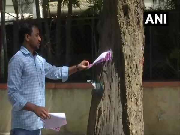 Vinod Kartavya removes a poster from a tree in Bengaluru. (Photo/ANI)