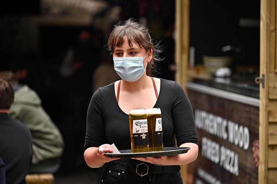 EDINBURGH, SCOTLAND - APRIL 26: A waitress serves members of the public drinks at the Three Sisters Pub in the Cowgate as lockdown measures are eased on April 26, 2021 in Edinburgh, United Kingdom. Cafes, beer gardens, non-essential shops and museums are reopening in Scotland today as lockdown easing continues. (Photo by Jeff J Mitchell/Getty Images)