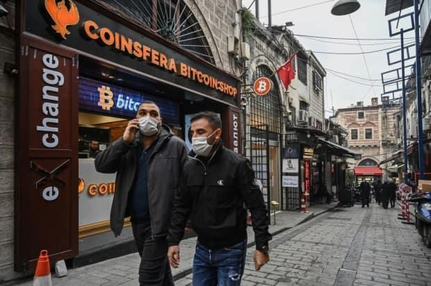 People pass in front of a crypto currency 'Bitcoin Change' shop near the Grand Bazaar on December 17, 2020 in Istanbul.