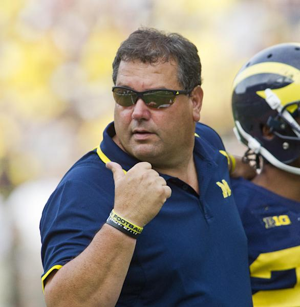 Michigan head coach Brady Hoke talks with his defenders during a time out in the fourth quarter of an NCAA college football game against Central Michigan, Saturday, Aug. 31, 2013, in Ann Arbor, Mich. Michigan won 59-9. (AP Photo/Tony Ding)