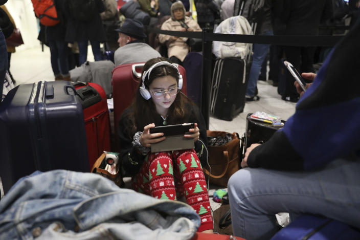 Passengers at Gatwick airport settle down to wait for their flights following the delays and cancellations brought on by drone sightings near the airfield, in London, Friday Dec. 21, 2018. New drone sightings Friday caused fresh chaos for holiday travelers at London's Gatwick Airport. (John Stillwell/PA via AP)