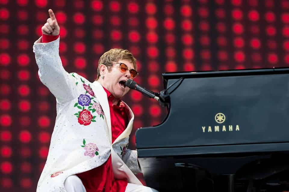 Elton John plays a piano and sings