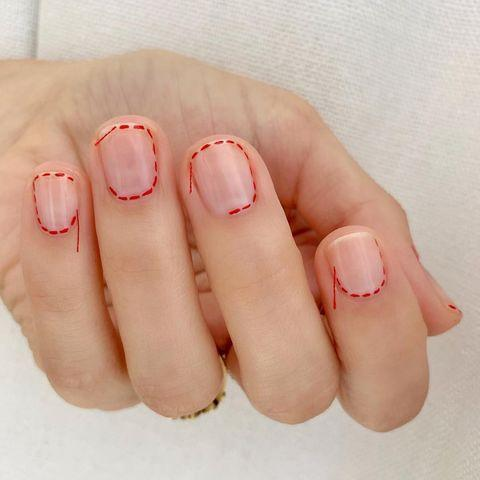 """<p>Nail artist Betina Goldstein glued red stitching around a sheer nude manicure, resulting in one of the coolest nail art looks we've seen this year.</p><p><a href=""""https://www.instagram.com/p/Btdnc1vABwI/"""" rel=""""nofollow noopener"""" target=""""_blank"""" data-ylk=""""slk:See the original post on Instagram"""" class=""""link rapid-noclick-resp"""">See the original post on Instagram</a></p>"""