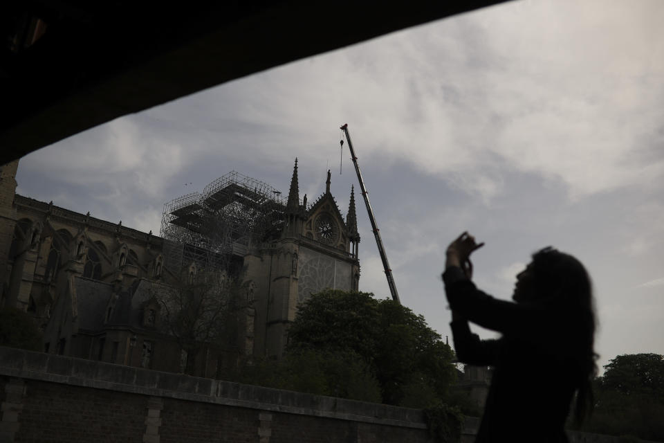 A woman takes photographs of the Notre Dame cathedral in Paris, Monday, April 22, 2019. In the wake of the fire last week that gutted Notre Dame, questions are being raised about the state of thousands of other cathedrals, palaces and village spires that have turned France — as well as Italy, Britain and Spain — into open air museums of Western civilization. (AP Photo/Francisco Seco)