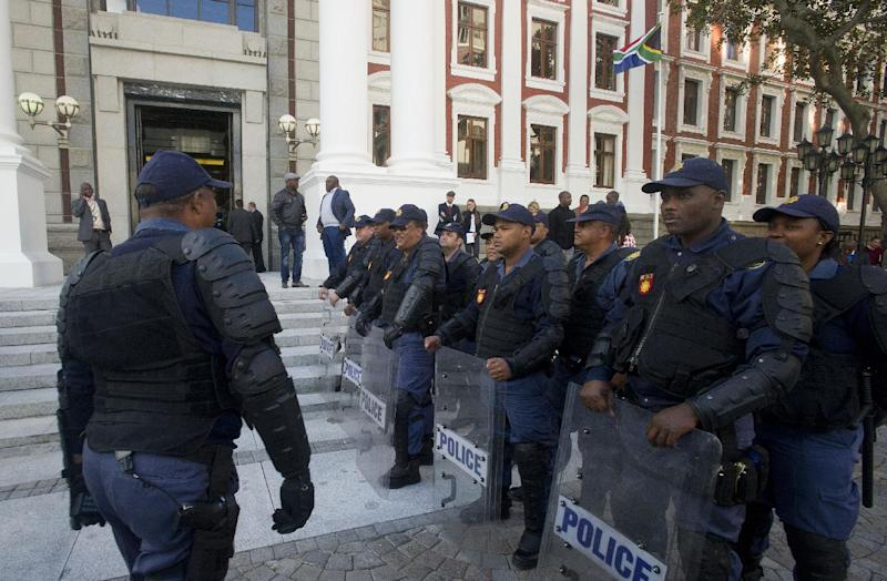 South African riot policemen line up outside the parliament following a scuffle in the general assembly in Cape Town on August 21, 2014