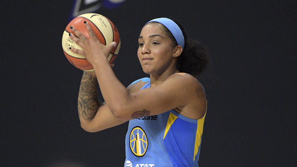 Gabby Williams sets up a play during a Chicago Sky game. She is holding the ball in both hands near her head and looking forward.