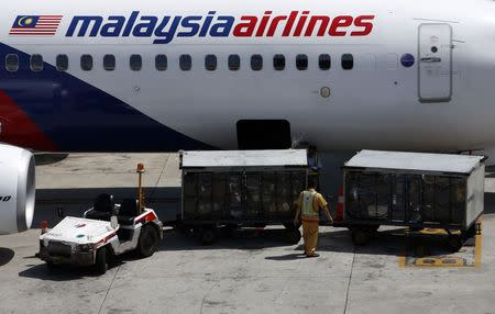 File photo of serviceman loading luggage into Malaysia Airlines plane at Kuala Lumpur International Airport in Sepang