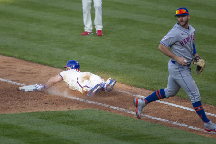 Philadelphia Phillies' Bryce Harper slides into first base on a bunt before New York Mets first baseman Pete Alonso could make the tag during the fifth inning of a baseball game Wednesday, April 7, 2021, in Philadelphia. (AP Photo/Laurence Kesterson)