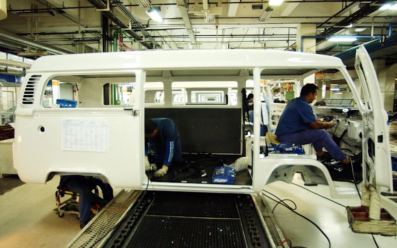 Auto workers install carpeting and the dash panel of a new, 2003 Volkswagen van at the company's factory in Sao Bernardo do Campo, 20 miles from Sao Paulo, Brazil, on Aug. 12, 2003. Brazil is the only place in the world where the classic vehicle is still being produced, after Volkswagen's Mexican division stopped making it last December. Virtually all of the vans, known locally as Kombis, are painted white because Brazilian businesses paint colorful ads on the vans that show up better against a white background. (AP Photo/Alexandre Meneghini) - Credit: Alexandre Meneghini/AP