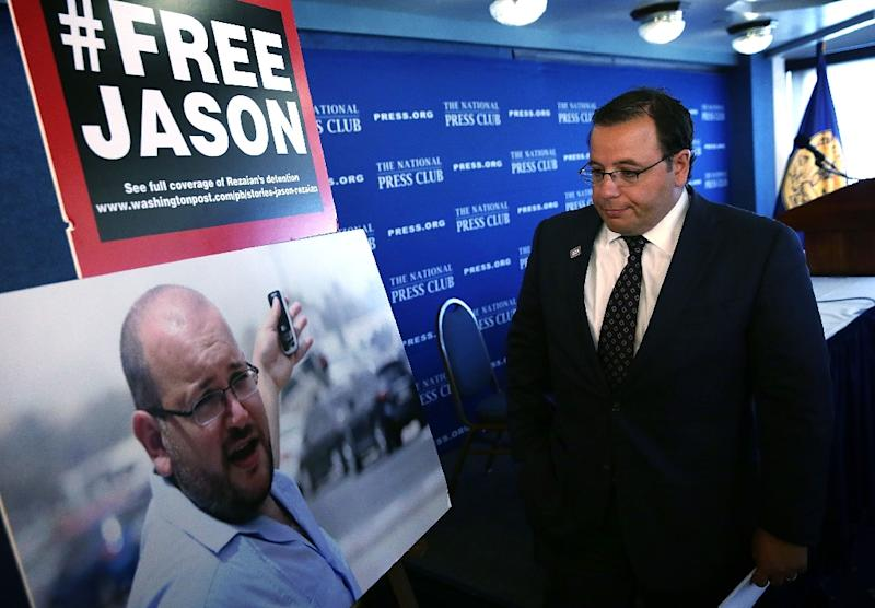 Ali Rezaian looks at a picture of his brother, Washington Post Tehran bureau chief Jason Rezaian, after a news conference at the National Press Club on July 22, 2015 in Washington, DC