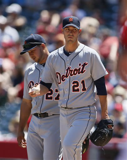 Detroit Tigers' starting pitcher Rick Porcello, right, and shortstop Jhonny Peralta, left, react after Los Angeles Angels Peter Bourjos reached first safely on an infield single during the first inning of a baseball game on Saturday, April 20, 2013, in Anaheim, Calif. (AP Photo/Danny Moloshok)