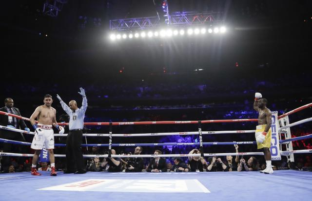 The referee stops the fight during the sixth round when England's Amir Khan could not continue after a low blow by Terence Crawfordin a WBO world welterweight championship boxing match Sunday, April 21, 2019, in New York. Crawford won the fight. (AP Photo/Frank Franklin II)