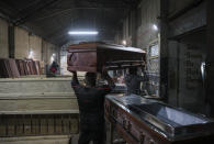 Cesar Ambrosio helps his father carry a coffin at the Bergut Funeral Services factory in Santiago, Chile, Thursday, June 18, 2020. Coffin production has had to increase up to 120%, according to Nicolas Bergerie, owner of the factory. His more basic coffin model is called the COVID model and is made to cope with the increase of deaths during the coronavirus pandemic. (AP Photo/Esteban Felix)
