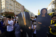 Cutouts of president-elect Joe Biden, left, and vice president-elect Kamala Harris are held up as people gather in Black Lives Matter Plaza to celebrate the presidential race being called in favor of Joe Biden over Pres. Donald Trump, Saturday, Nov. 7, 2020, in Washington. His victory came after more than three days of uncertainty as election officials sorted through a surge of mail-in votes that delayed the processing of some ballots. (AP Photo/Alex Brandon)