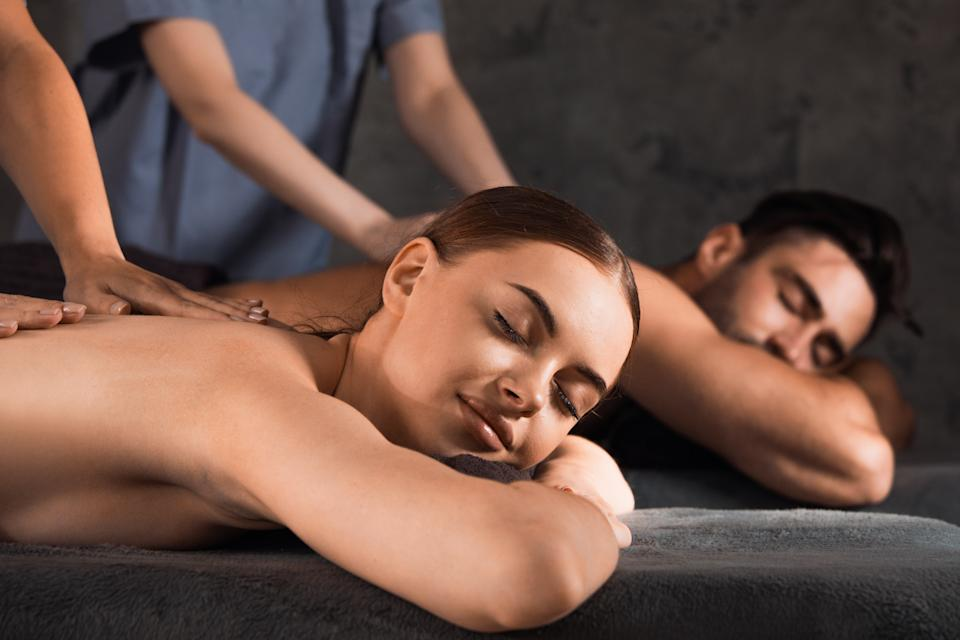 Beautiful couple relaxing together at spa centre at beauty treatment massage