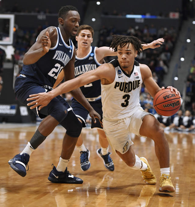 FILE - In this March 23, 2019, file photo, Purdue's Carsen Edwards, right, dribbles around Villanova's Dhamir Cosby-Roundtree, left and Collin Gillespie, back, during the second half of a second-round men's college basketball game in the NCAA tournament in Hartford, Conn. Edwards is an undersized point guard with big scoring potential in Thursday's NBA draft. (AP Photo/Jessica Hill, File)