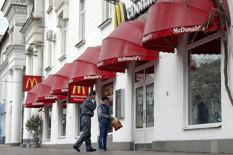 Men stand at the entrance of a closed McDonald's restaurant in Sevastopol on April 5, 2014