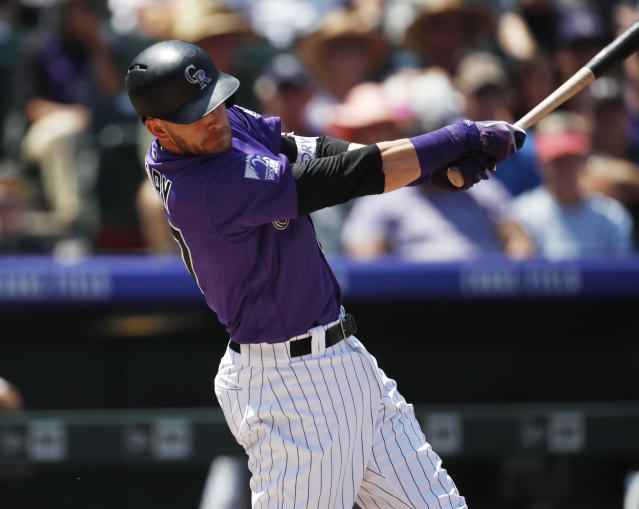 Colorado Rockies' Trevor Story connects for a sacrifice fly to bring in a run off Los Angeles Dodgers starting pitcher Rich Hill in the first inning of a baseball game Sunday, Aug. 12, 2018, in Denver. (AP Photo/David Zalubowski)