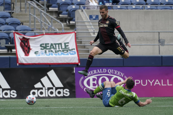 Atlanta United midfielder Brooks Lennon (11) jumps over Seattle Sounders midfielder Joao Paulo during the first half of an MLS soccer match, Sunday, May 23, 2021, in Seattle. (AP Photo/Ted S. Warren)