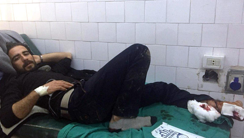 In this photo released by the Syrian official news agency SANA, A Syrian man receives treatment after U.S. troops opened fire on locals who tried to block a U.S. convoy driving near the village Khirbet Ammu, east of Qamishli city, Syria, Wednesday, Feb. 12, 2020. SANA said the locals had gathered at an army checkpoint, pelting the U.S. convoy with stones and taking down a U.S. flag flying on a vehicle when troops fired with live ammunition and smoke bombs. (SANA via AP)