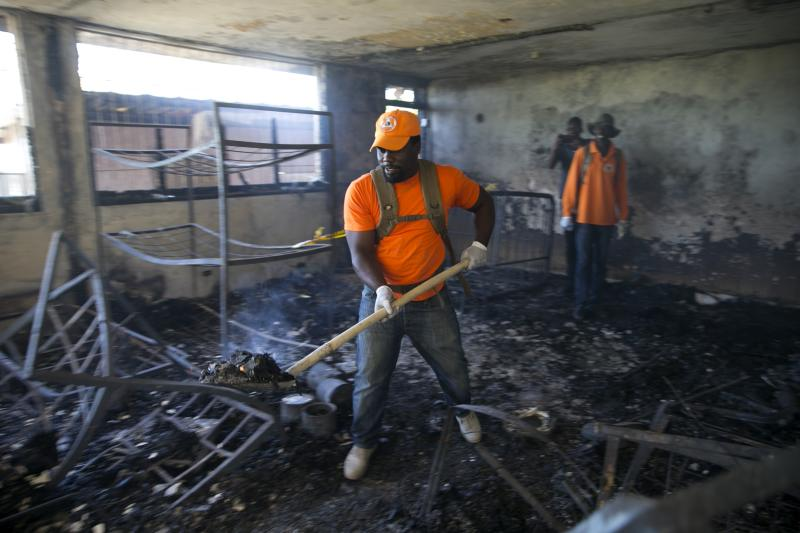 A civil protection worker shovels charred debris from inside the Orphanage of the Church of Bible Understanding where a fire broke out the previous night in Kenscoff, on the outskirts of Port-au-Prince, Haiti, Friday, Feb. 14, 2020. A fire swept through this Haitian children's home run by a Pennsylvania-based nonprofit group, killing 13 children, health care workers said Friday.  (AP Photo/Dieu Nalio Chery)