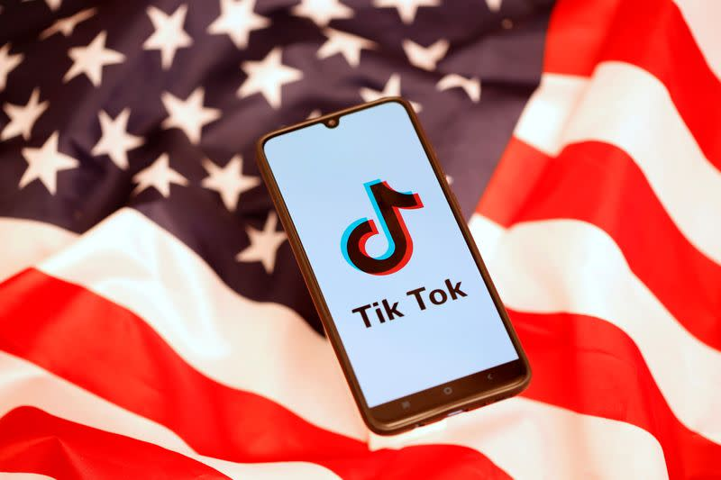 TikTok logo is displayed on the smartphone while standing on the U.S. flag in this illustration