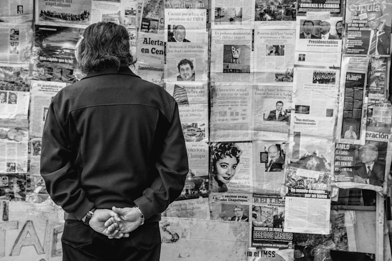 Rear View Of Man Standing Against Newspapers On Wall