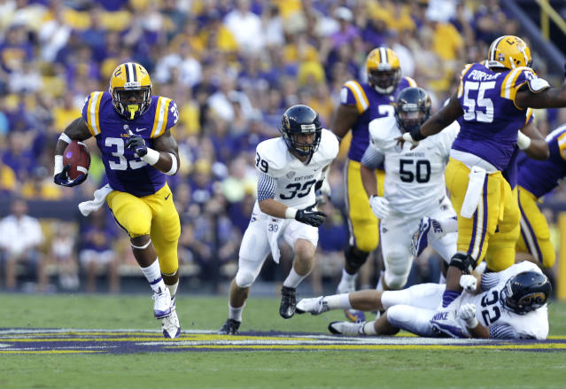 LSU running back Jeremy Hill (33) carries for a touchdown past Kent State linebacker Jake Houts (35), defensive tackle Chris Fairchild (50) and linebacker Matt Dellinger (32) in the first half of an NCAA college football game in Baton Rouge, La., Saturday, Sept. 14, 2013. (AP Photo/Gerald Herbert)