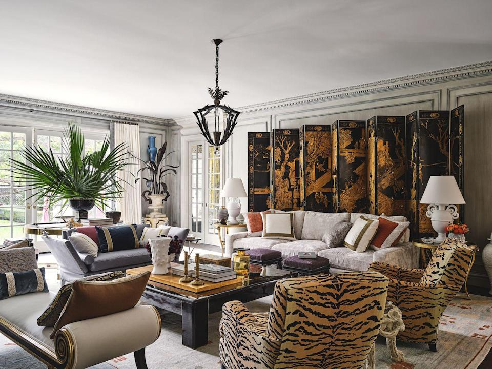 """<p>It was the crown molding that held inspirational magic for designer <a href=""""https://aiduss.com/"""" rel=""""nofollow noopener"""" target=""""_blank"""" data-ylk=""""slk:Michael Aiduss"""" class=""""link rapid-noclick-resp"""">Michael Aiduss</a> in the home's light-drenched living room. The intersection of four passageways previously was home to some mediocre built-ins, but with enchanting trim crafted locally by Casci Ornamental Plaster, Aiduss began envisioning a conceptual client who was a Parisian socialite who had recently married a Texan and was relocating to Dallas.</p><p> Immersing himself in classic French interiors from the 1920s to the 1960s—as well as historic rooms from all over Western Europe—the designer sought to create a room that """"feels rooted in classicism and filled with a generation of beautiful, collected items. I want people to feel like they'd just been transported to a chic French home or hotel, a place that is atmospheric and evocative in the wonderment of these exciting items, both classic and modern.""""</p><p>This living room features a collection of notable pieces, from a Karl Springer coffee table (inspired by Jean-Michel Frank) to a 19th-century black and gold Chinese screen as well as vintage chairs covered in Pierre Frey tiger-print linen. Aiduss worked with local decorative painter Barry Martin to add patina to the walls and, in collaboration with The Shade Store, he created breezy drapery that features trim from his brand-new collection with Houles. </p><p>""""The fireplace area sums me up completely as it's bold, clean, and classic, with a flair of modernist touches,"""" says Aiduss. """"This space offers a sense of luxury that is also comfortable because I didn't want it to be a one-hit-wonder room. I want people to experience this space and feel like it's attainable for them.""""</p>"""