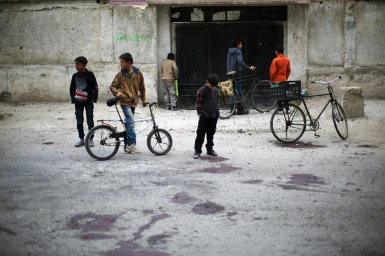 Syrian children stand at the blood stained scene of a reported government shelling that killed schoolchildren in the rebel-held besieged town of Jisreen, east of the capital Damascus, on October 31, 2017