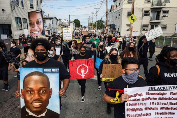 PHOTO: A marcher carries a sign with an image of Ahmaud Arbery, left, during a peaceful protest on June 9, 2020 in Revere, Mass., for Black Americans killed at the hands of law enforcement. (Boston Globe via Getty Images, FILE)