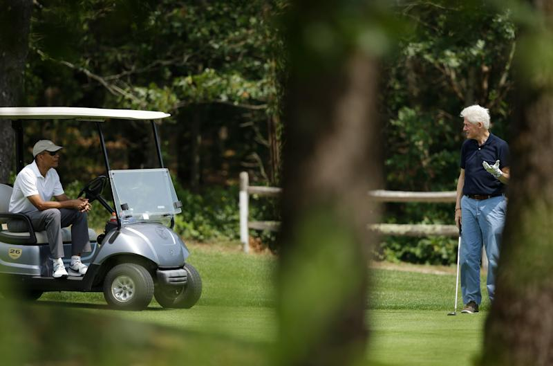 President Barack Obama, left, sits in a cart while talking with former President Bill Clinton, right, as they golf Saturday, Aug. 15, 2015, at Farm Neck Golf Club, in Oak Bluffs, Mass., on the island of Martha's Vineyard. (AP Photo/Steven Senne)