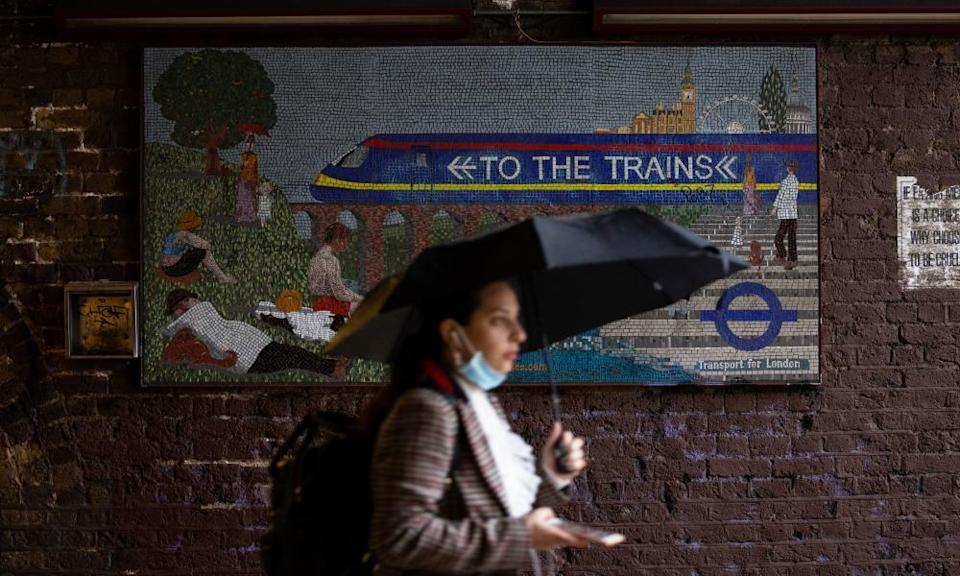 A woman with an umbrella walking past a mosaic sign saying