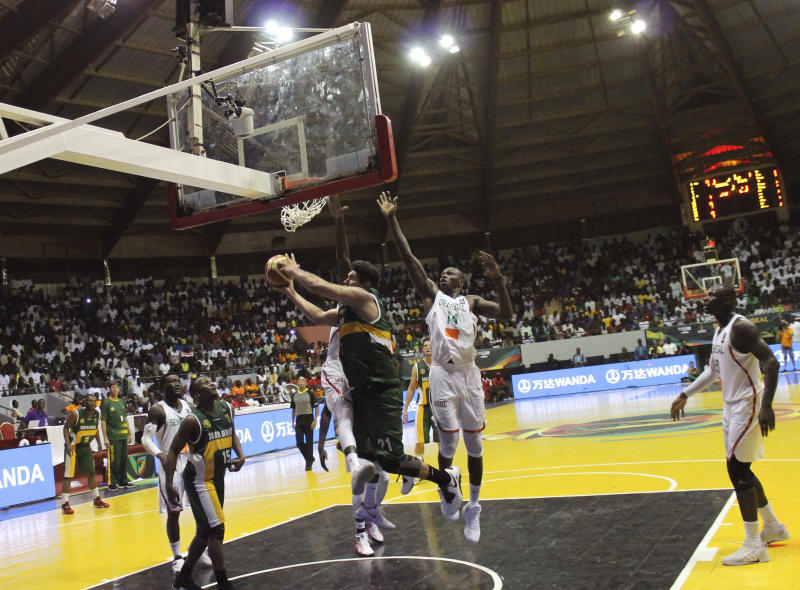 South Africa's Chris Gabriel, center front, launches a hook shot over Senegal's Gorgui Dieng during AfroBasket tournament at Marius Ndiaye stadium in Dakar, Senegal, Friday, Sept. 8, 2017. The African basketball championship may lack star power, even electrical power on occasion. But with national pride at stake, it almost always entertains. AfroBasket, which tipped off Friday in Senegal and Tunisia, can't be compared to a glitzy event like the NCAA tournament. Senegal's aging national stadium in the capital Dakar, for example, has no air conditioning. A recent women's AfroBasket game in Mali was paused because of a power cut. (AP Photo/ Ken Maguire)