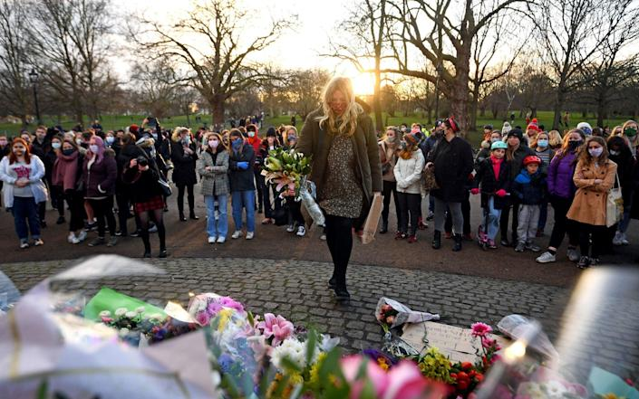 A woman leaves floral tributes for Sarah Everard - Victoria Jones/PA