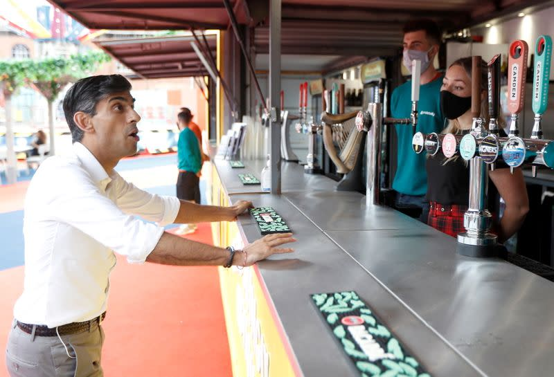 FILE PHOTO: Britain's Chancellor Rishi Sunak speaks with previously furloughed staff at the London Wonderground comedy and music festival venue in London