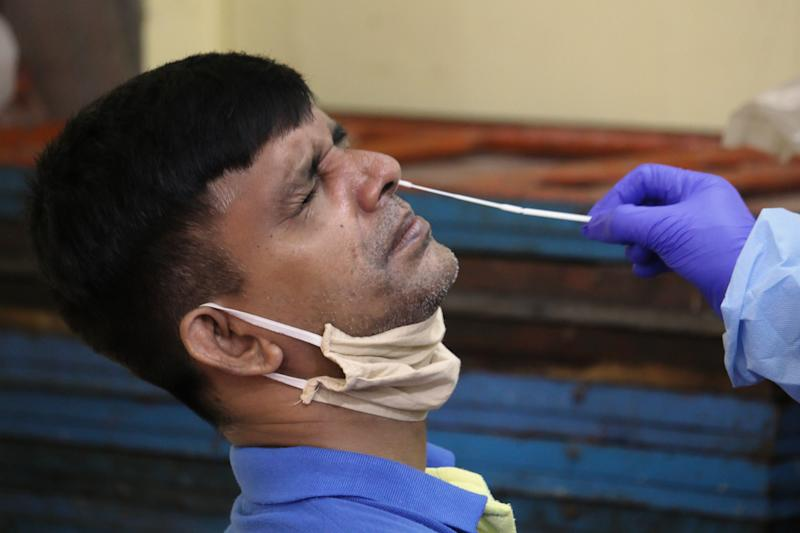 A healthcare worker collects nose-swab samples from a man during a medical check-up in Mumbai, India on July 24, 2020. India has become the third country after the United States and Brazil, to cross 01 million COVID-19 cases. (Photo by Himanshu Bhatt/NurPhoto via Getty Images)