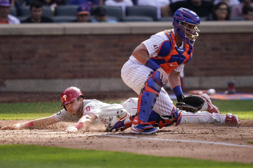 Philadelphia Phillies' Nick Maton, left, slides past New York Mets catcher James McCann to score on a double by Aaron Nola during the fifth inning of the first baseball game of a doubleheader Friday, June 25, 2021, in New York. (AP Photo/Frank Franklin II)
