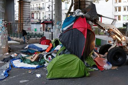 Workers clean a dismantled makeshift camp in a street near Stalingrad metro station in Paris after the evacuation of thousands of migrants